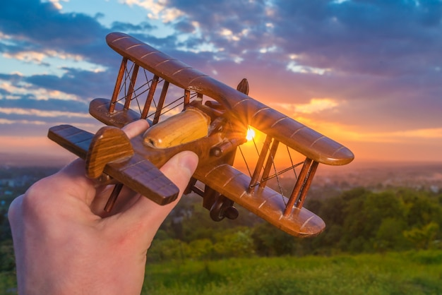 The hand hold wooden plane on the background of a sunset
