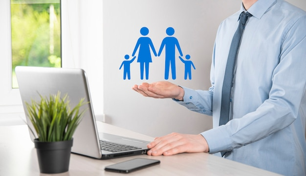 손을 잡고 젊은 가족 아이콘. 가족 생명 보험, 지원 및 서비스, 가족 정책 및 지원 가족 개념. 행복한 가족 개념입니다. 공간 복사. 종이 남자 가족을 보여주는 mancupped 손.