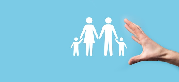 Hand hold young family icon. family life insurance,supporting and services,family policy and supporting families concepts.happy family concept.copy space.mancupped hands showing paper man family