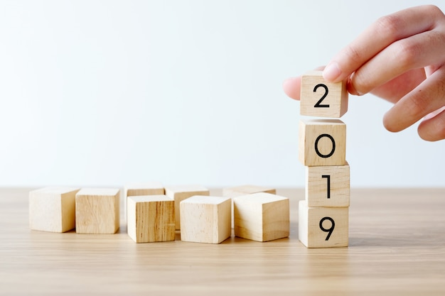 Hand holding 2019 happy new year wood cubes on table background