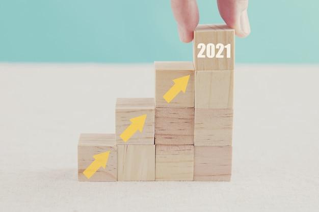 Рука, держащая 2021 год и стрелы вверх по деревянным блокам