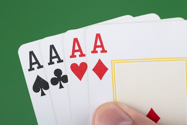 Hand holding 4 aces cards over green background.