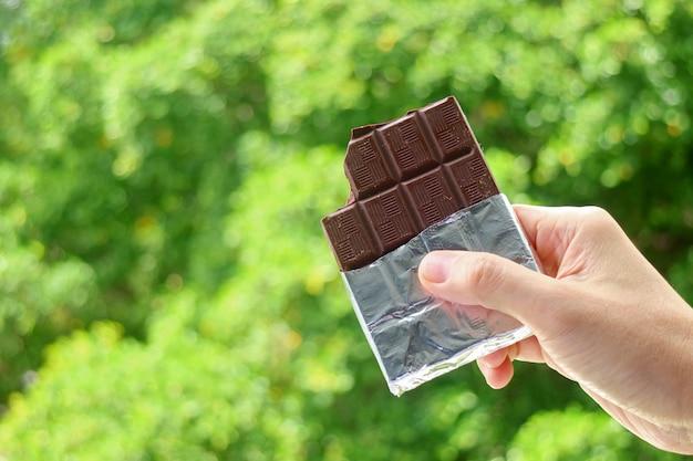 背景にぼやけた緑の葉とフォイルパックでダークチョコレートのバーを持っている手