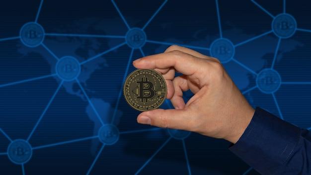 Рука, держащая биткойн над цифровой криптовалютой