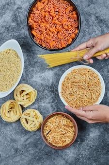 Рука держит миску сухой пасты с различными видами сырых макарон на мраморном столе.