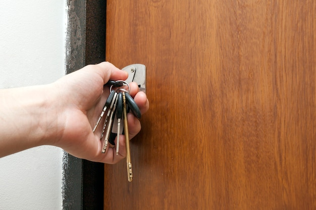 鍵穴にさまざまな鍵の束を持っている手
