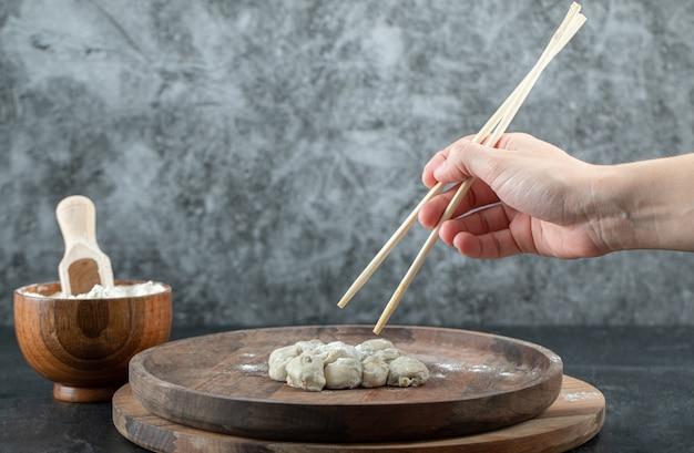Рука, держащая палочку для еды с клецкой.