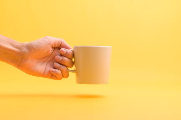 Рука держит чашку кофе, пьет кофе, чтобы дать энергию.