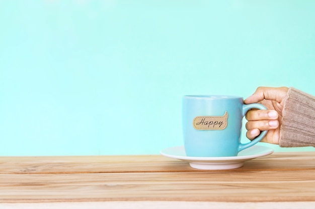 Рука с кружкой чашки кофе с ярлыком слова