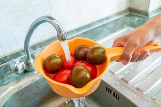 新鮮な果物とベリーのザルを持って、キッチンで水で洗う手