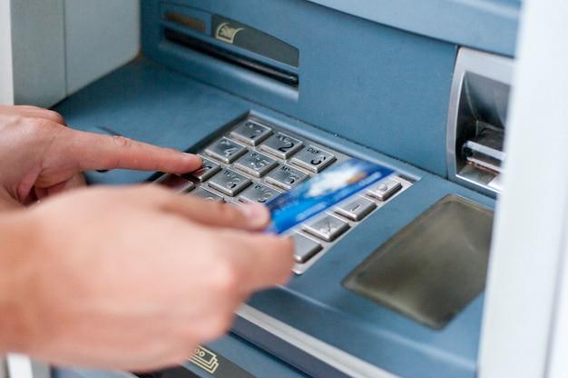 Atmの隣にクレジットカードを持っている手