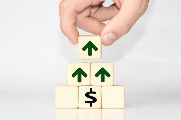 ドルの成長のシンボルで評価を上げるためにシンボルの付いた立方体を持っている手。テキストまたは見出し用のスペースをコピーする