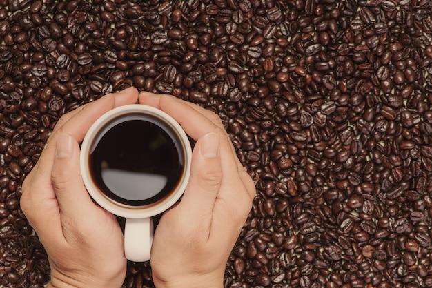 ブラックコーヒーとローストコーヒー豆のカップを持っている手。上から見る。