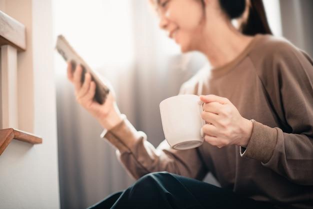 집에서 휴대 전화를 사용 하여 따뜻한 커피 한 잔을 들고 손.
