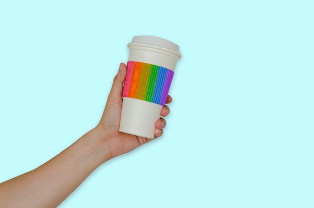 タンブラースリーブに虹色のコーヒーのカップを持っている手