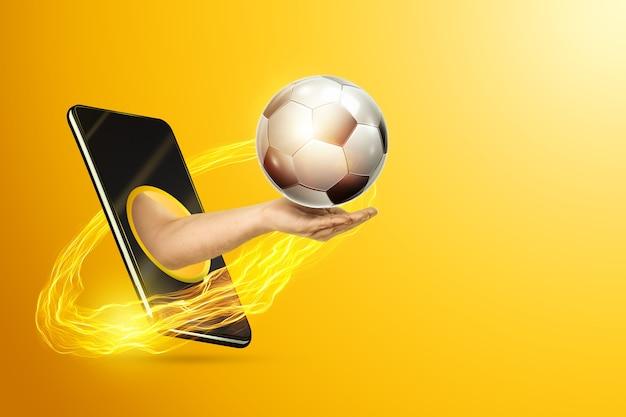 Рука держит футбольный мяч через смартфон