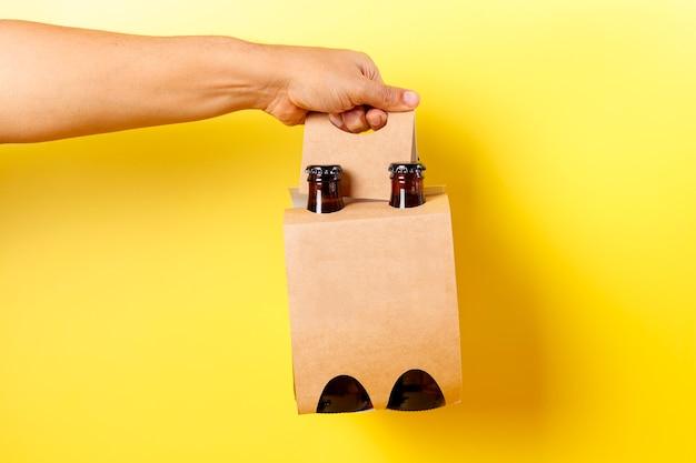 Рука держит презентацию из четырех пакетов пива с желтым фоном