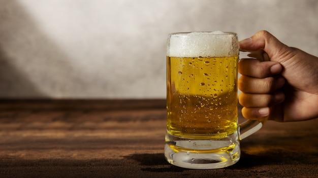テーブルの上にビールのグラスを持っている手