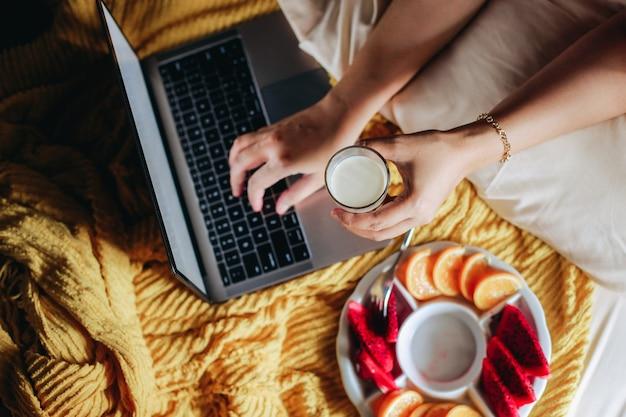 우유 한 잔을 들고 침대에 다양한 과일과 함께 노트북에 입력하는 손