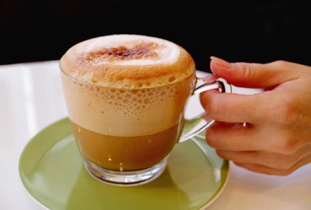 食欲をそそる泡立つカプチーノコーヒーのグラスを持っている手