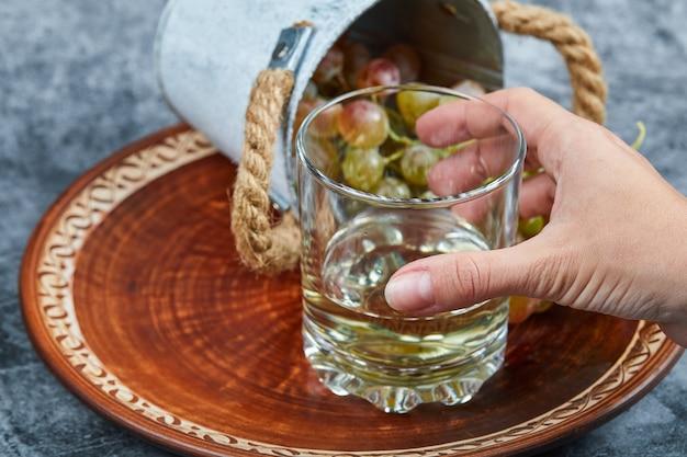 손을 대리석 배경에 화이트 와인 한 잔과 포도의 작은 양동이를 들고. 고품질 사진
