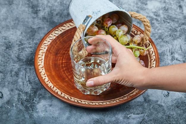 大理石の背景に白ワインのグラスとブドウの小さなバケツを持っている手。高品質の写真