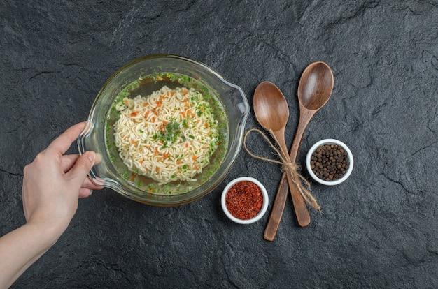 暗い面に美味しい麺が入ったガラス皿を持っている手。