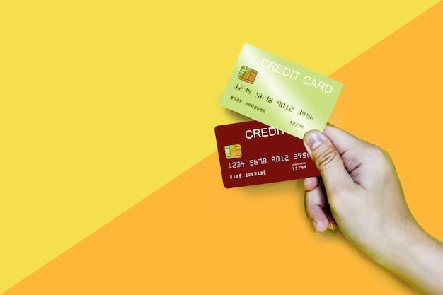 黄色とオレンジ色の背景に金と赤のクレジットカードを持っている手、2枚のクレジットカードを持っています。クレジットカードのクリッピングパス。