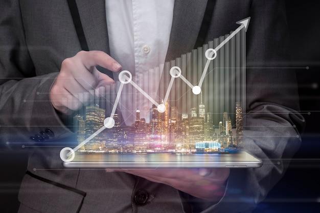 Рука держит ноутбук с интеллектуальными услугами для успешного инвестирования с графиком роста доходов