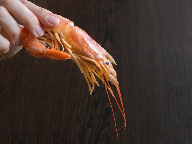 大きな新鮮なエビを持っている手。調理した新鮮な海老