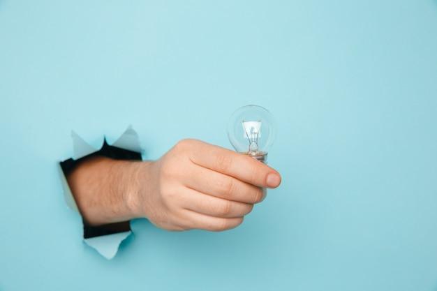 Рука лампочку от разорванного отверстия в синей бумаге. концепция экономии энергии