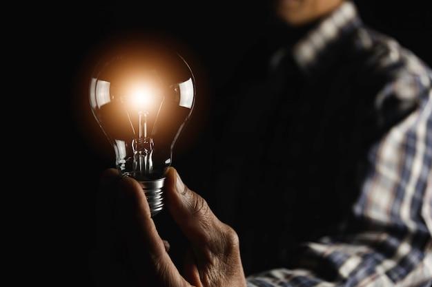 Рука держит лампочку. инновации и креативная концепция.