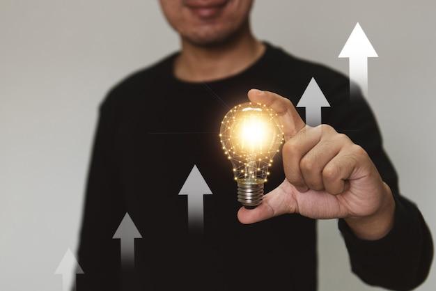 Рука, держащая лампочку, поднимается вверх с инвестиционной стрелкой для роста бизнеса