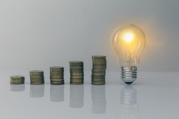 손을 동전 스택과 전구를 잡고입니다. 돈 개념을 저장하기위한 창의적인 아이디어. 미래를위한 자금 관리.