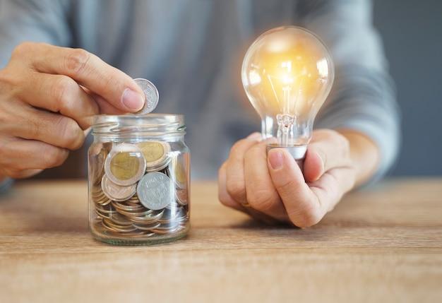 コインスタックで電球を持っている手。お金の概念を節約するための創造的なアイデア。将来のためのお金の管理