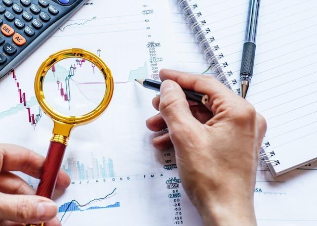 손을 잡고 경제 차트 위에 돋보기와 연필