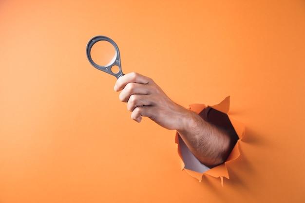 オレンジ色の背景に虫眼鏡を持っている手