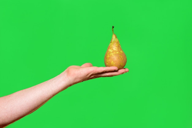 Рука держит грушу на зеленом фоне