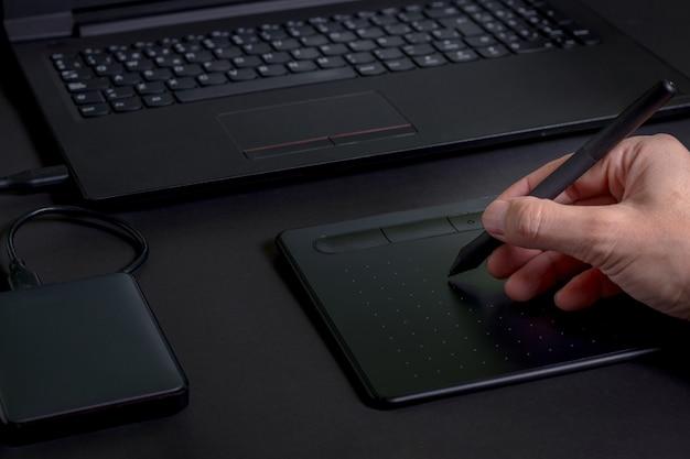 黒い背景の上のラップトップとハードドライブで、ペンタブレットを持っている手