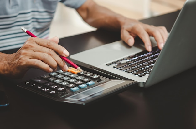 Рука, держащая карандаш, калькулятор и клавиатуру компьютера на столе.