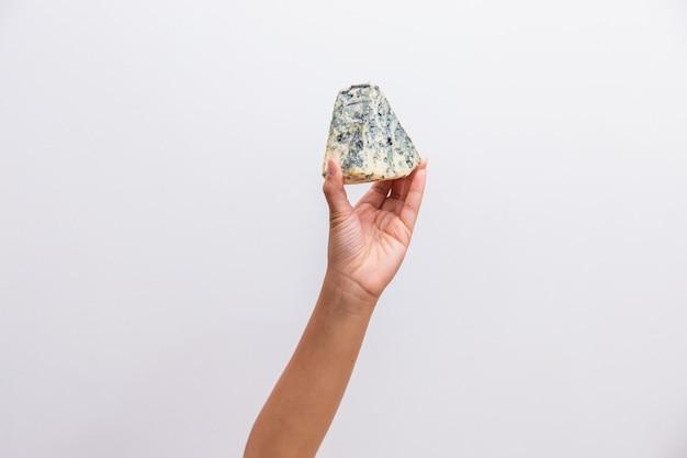 Рука держит кусок сыра горгонзола