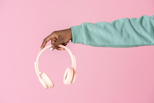 분홍색 헤드폰을 들고 있는 손
