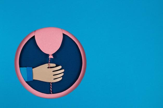 重なり合う青い丸い穴、ピンクの円のフレームにピンクの紙風船を持っている手。休日、誕生日、バレンタインのコンセプト。 3dペーパーアートと折り紙スタイル。イベントバナーポスターを祝う