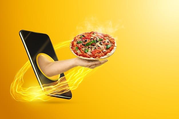 Рука держит пиццу через смартфон