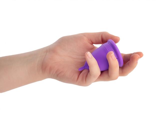 Рука держит фиолетовый менструальный кубок