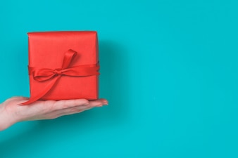 Hand holding a red gift on a blue background