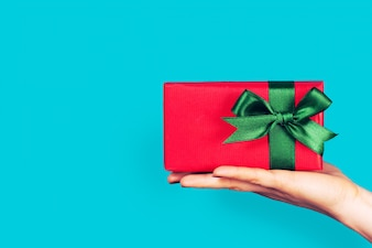 Hand holding a red gift with green bow