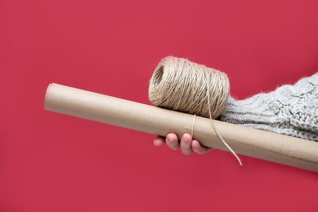 빨간색 배경에 크래프트 종이 한 롤과 로프 릴을 들고 있는 손을 클로즈업합니다. 복고 스타일 컨셉으로 자신의 손으로 선물 포장.