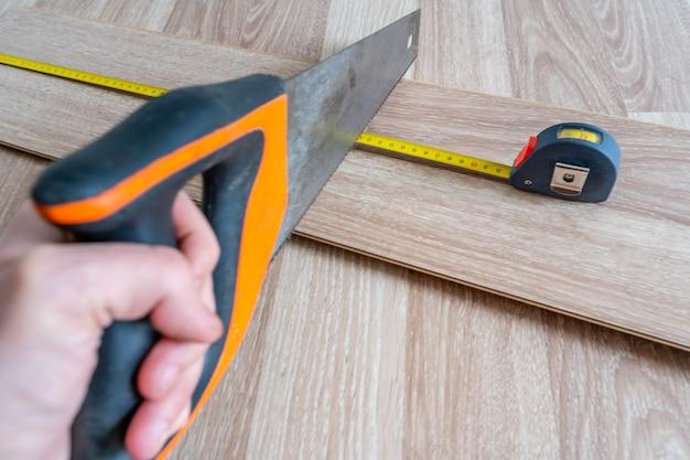 黄色の巻尺で測定されたラミネートボードを準備するためののこぎりを持っている手。
