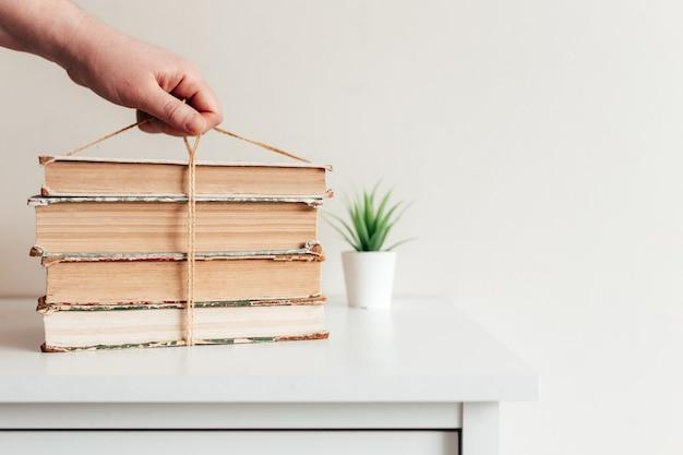 Рука, держащая стопку старых книг, концепция обучения, учебы и образования, концепция науки, мудрости и знаний